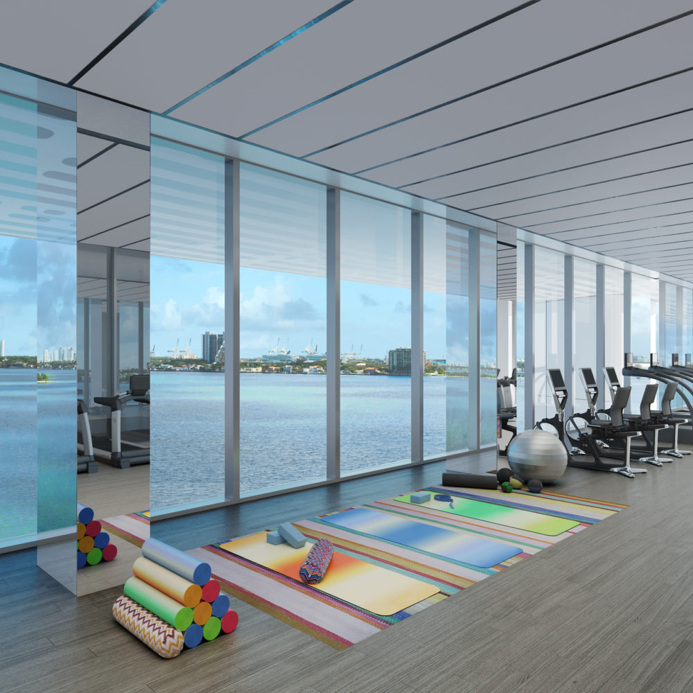 Interior view of Missoni Baia residence gym with full view of the ocean. Has stretching mats and cardio equipment.