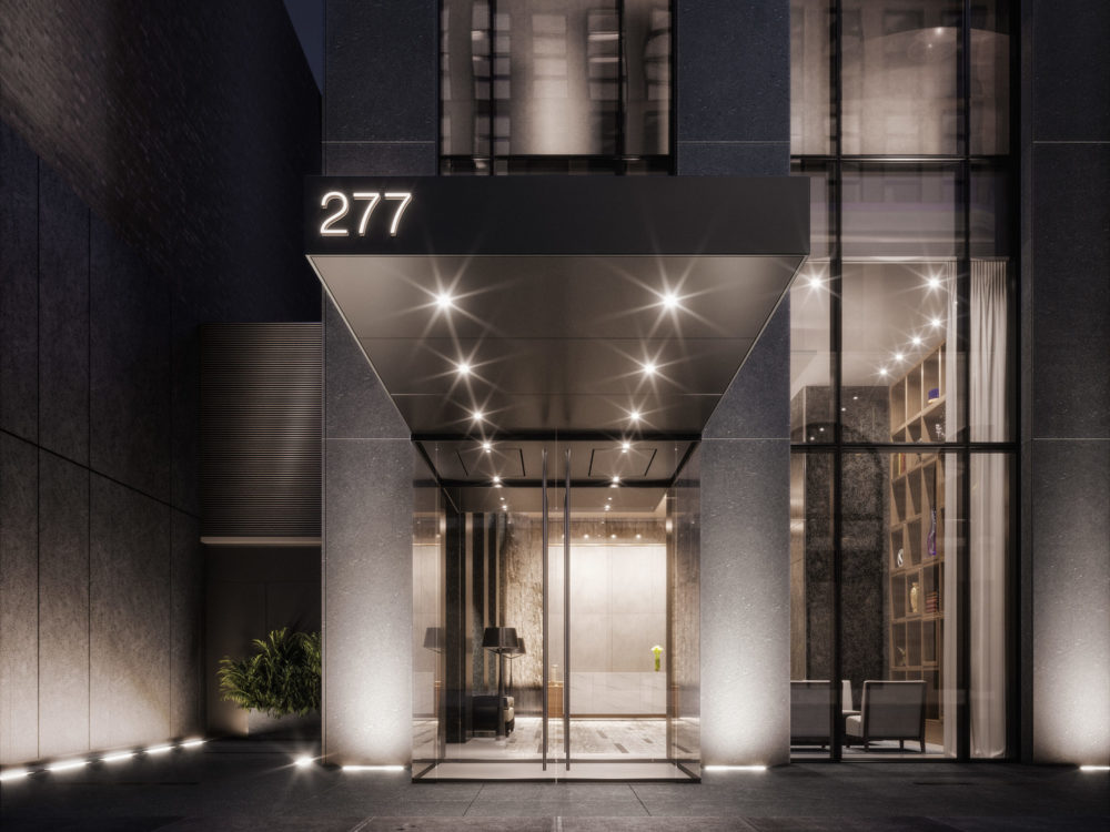 Exterior view of entry to 277 Fifth Avenue condominium in New York City. Includes lights and light exterior during the night.