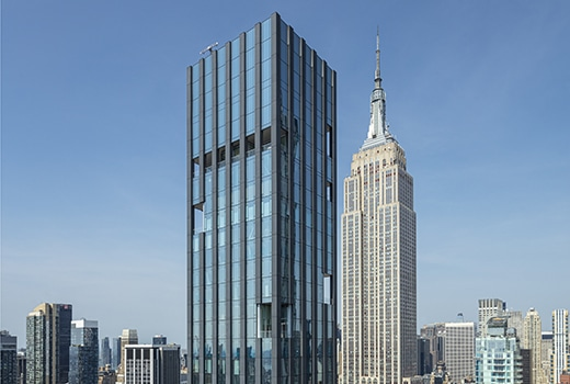 Exterior aerial view of 277 Fifth Avenue condominiums. Includes view of New York City and detailed architectural building.