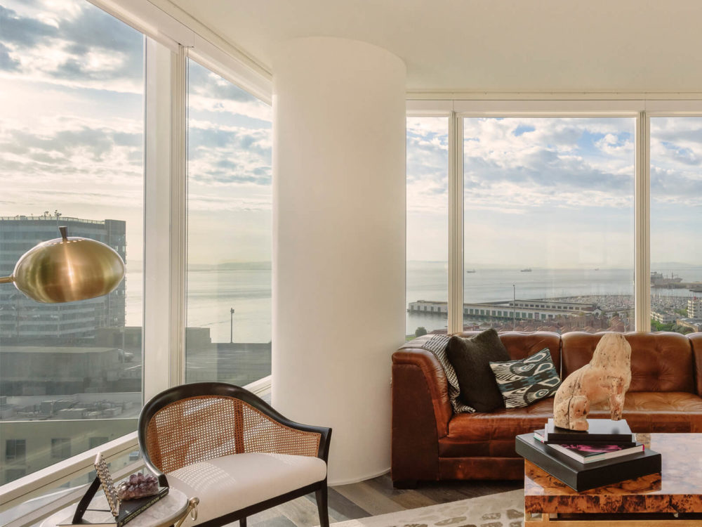 Corner living room at The Harrison luxury condos in San Francisco. Furniture in front of oversized windows with city views.