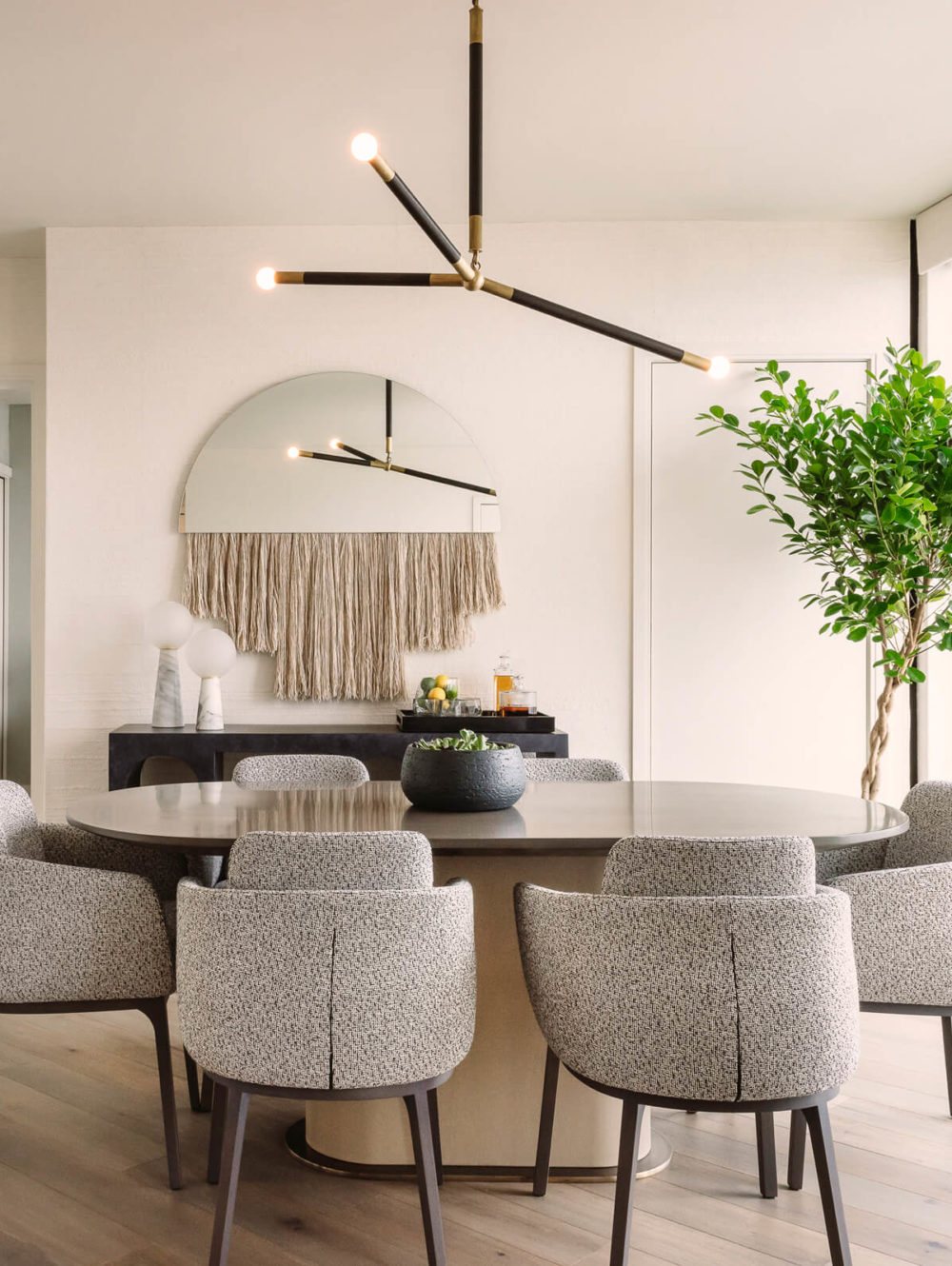 Dining table with a chandelier hanging above, white walls, and large windows at The Harrison luxury condos in San Francisco.