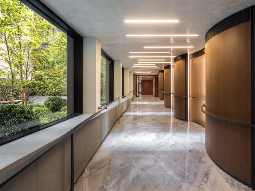 Interior view of 70 Charlton condominiums lobby hallway in New York City. Has marble floor and brown, lit walls.