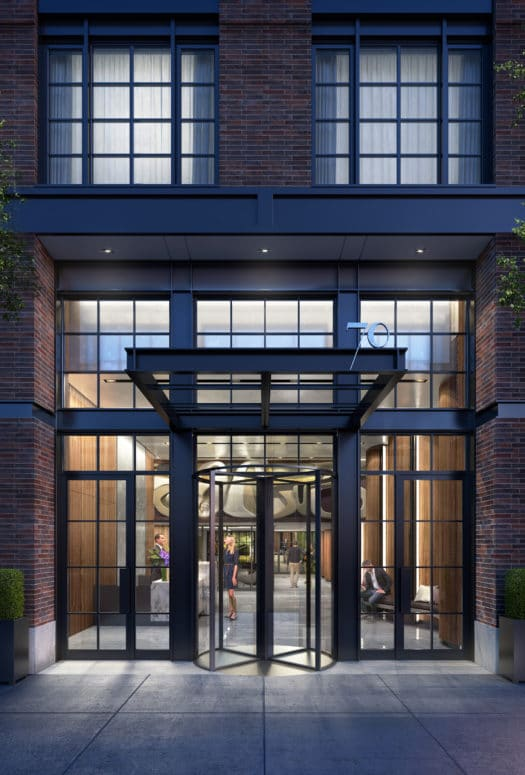 Exterior view of the entrance to 70 Charlton condominiums lobby in New York City. Has black framed windows and rotating door.