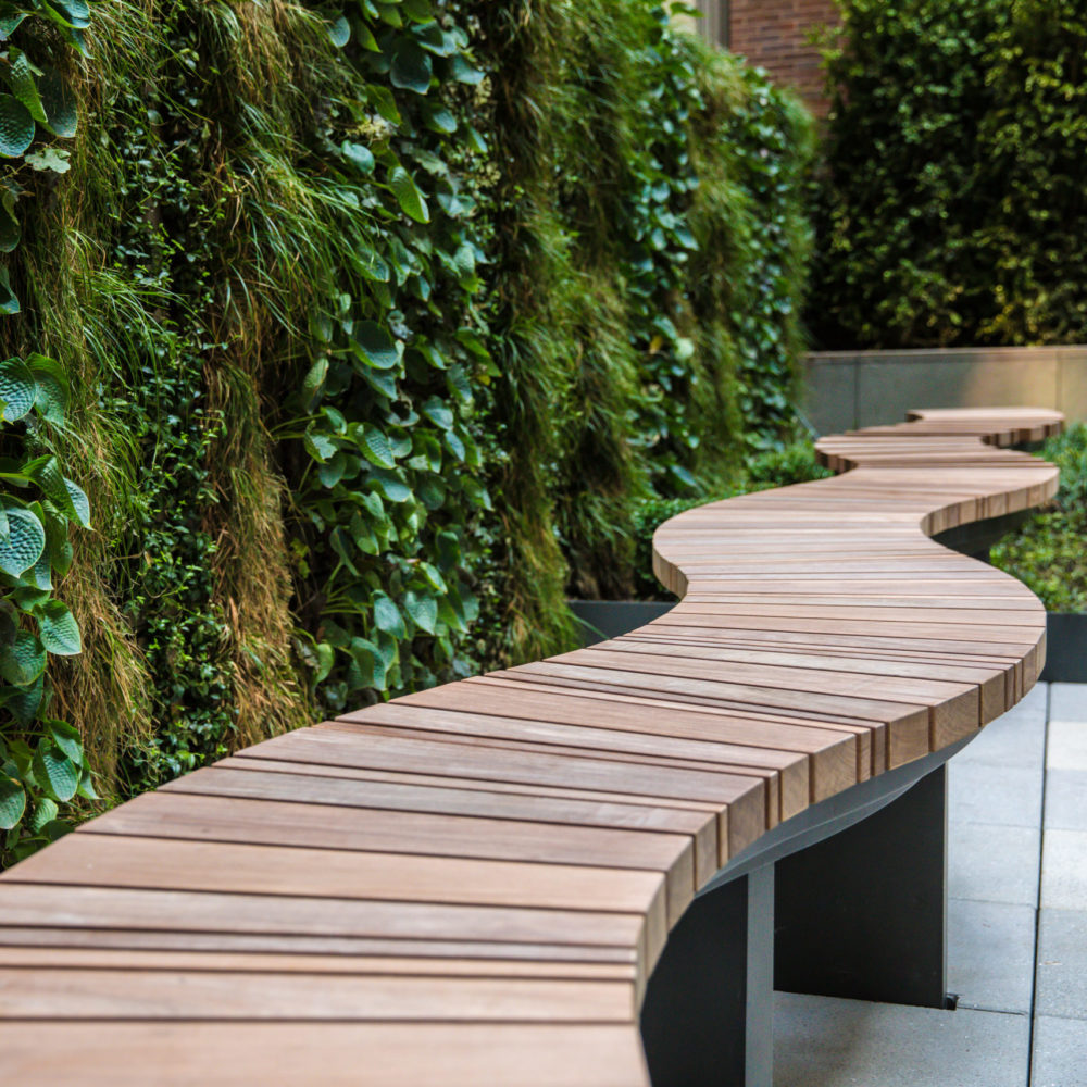 Exterior closeup view of 70 Charlton condominiums courtyard in New York City. Has wood bridge walkway and green trees.