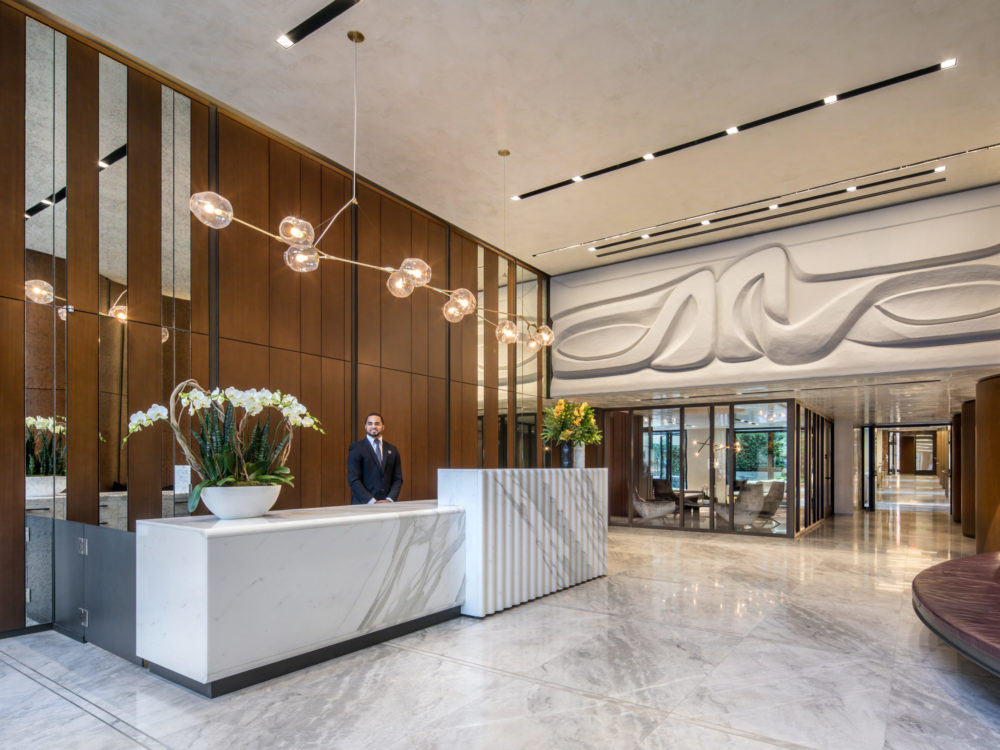 Interior view of 70 Charlton condominiums lobby in New York City. Has white receptionist desk and wood paneling.