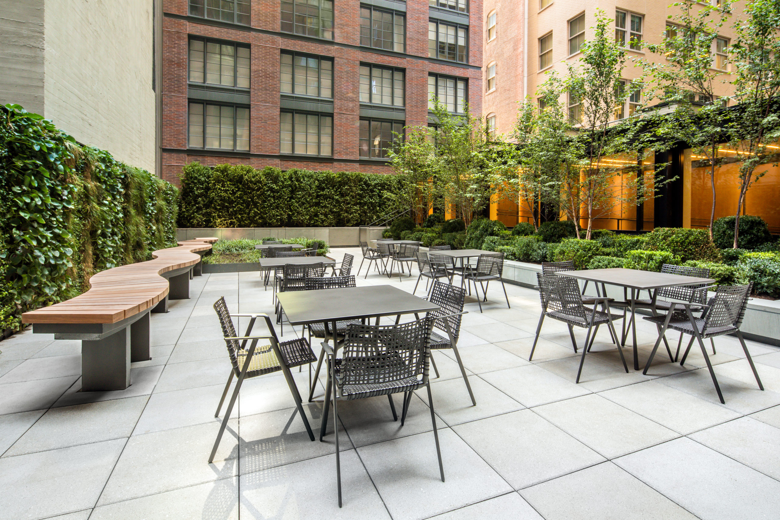 Exterior view of 70 Charlton condominiums outdoor lounge in New York City. Has dining tables, tile floors and green bushes.