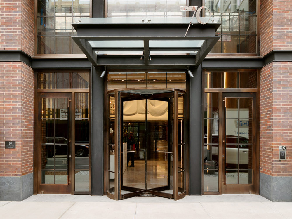 Exterior view of 70 Charlton condominiums lobby entrance in New York City. Has brick walls and black window frames.