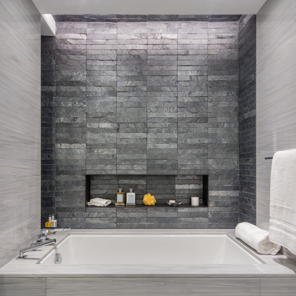 Interior view of 70 Charlton residence bathroom in New York City. Has tile walls, white bathtub and towels.