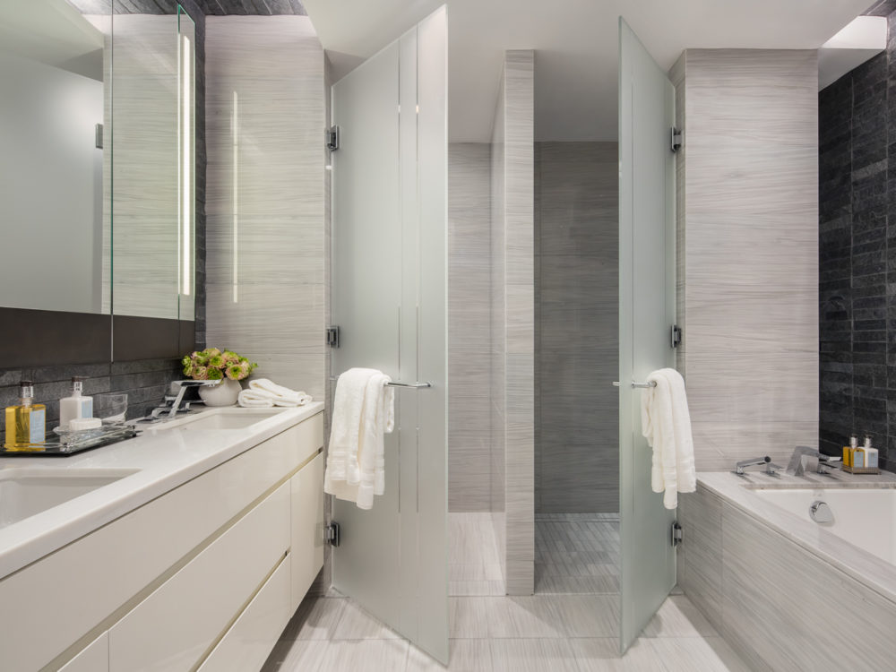 Interior view of 70 Charlton residence bathroom in New York City. Has white bathtub, white counters and glass shower door.