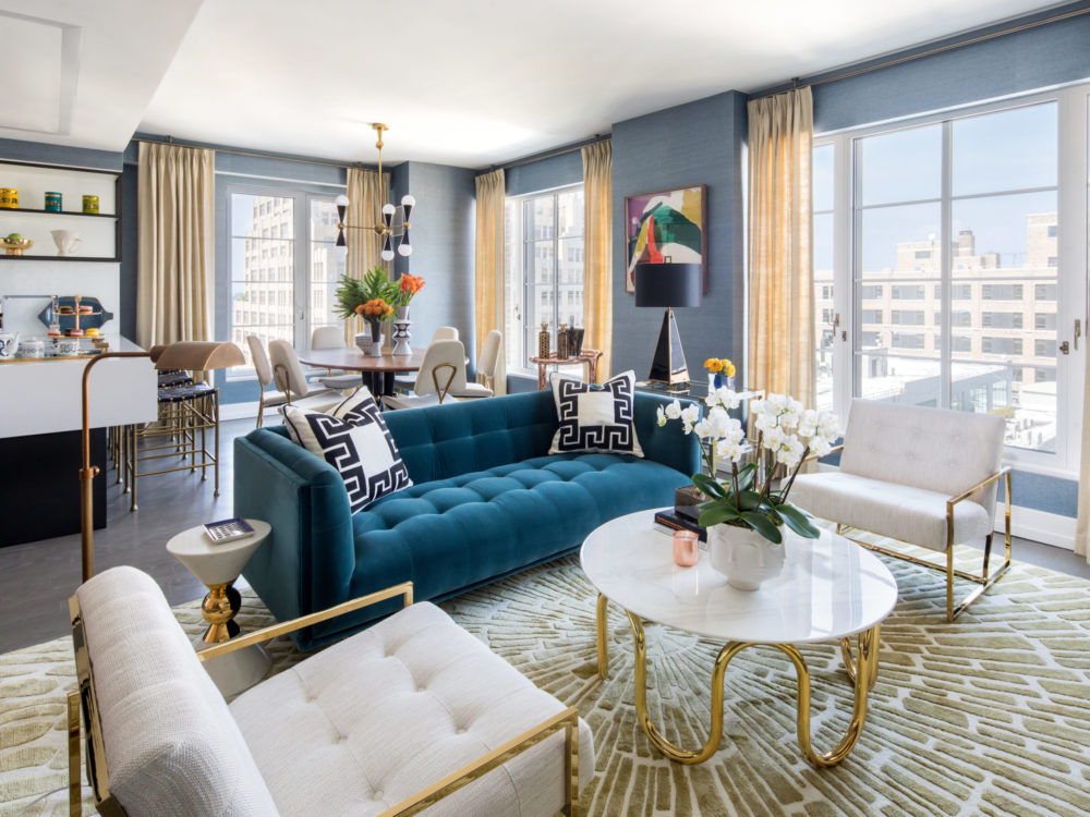 Interior view of 70 Charlton residence with window view of New York City. Has a blue couch, white chair and center table.