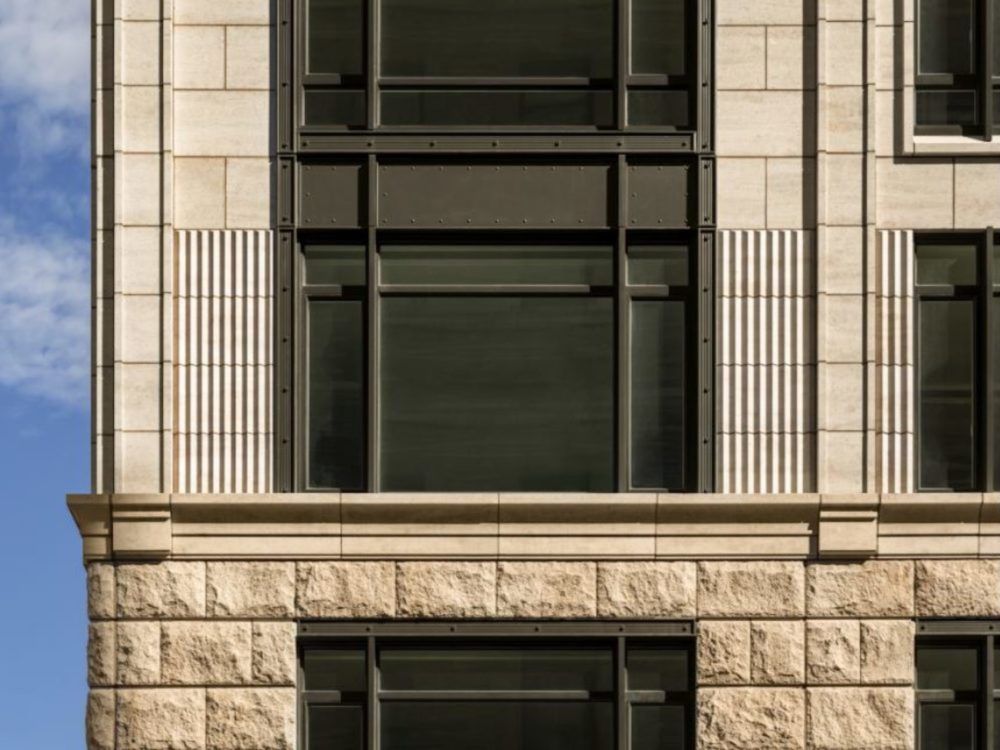 Close up of 70 Vestry luxury condos exterior in NYC. Light brick walls with dark metal finishes and large windows.