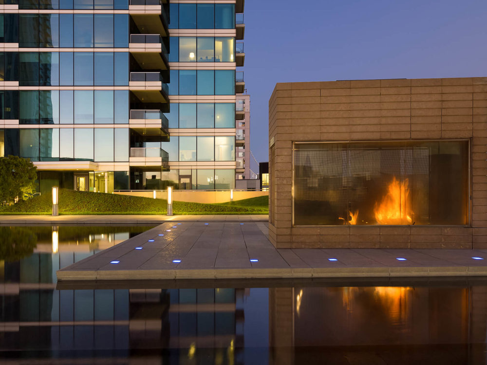 Terrace at The Harrison in San Francisco. Outdoor fireplace with large windows, a water feature and skyscraper in background.