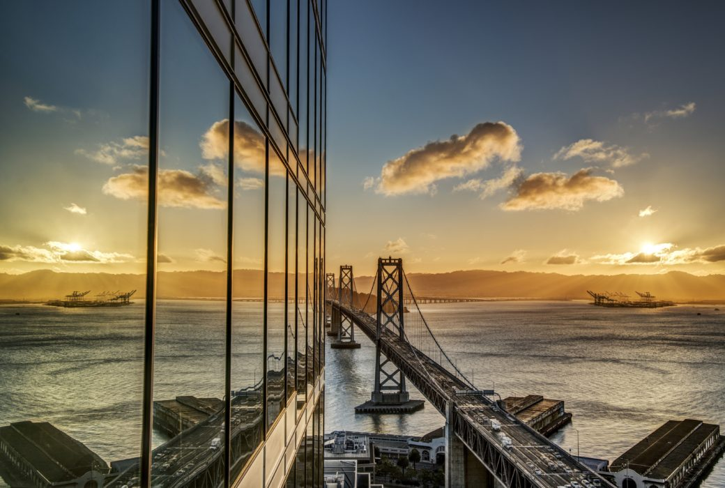 Exterior of The Harrison condos in San Francisco. Side of building with glass walls along the Bay Bridge during sunset.