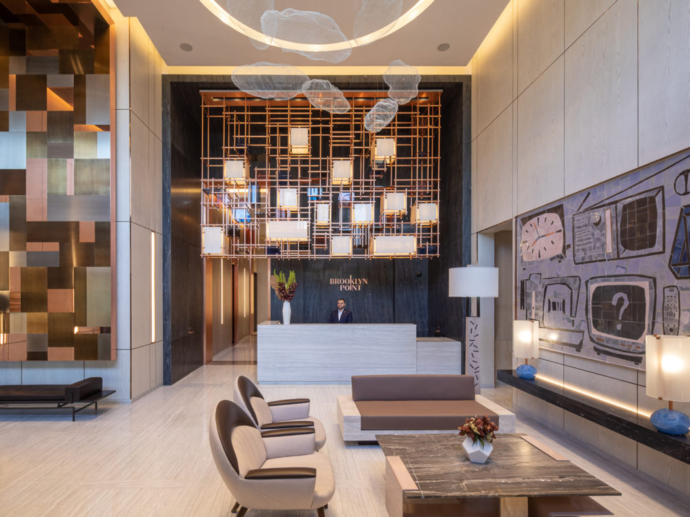 Interior view of Brooklyn Point condominiums lobby. Has patterned walls and lounging furniture.