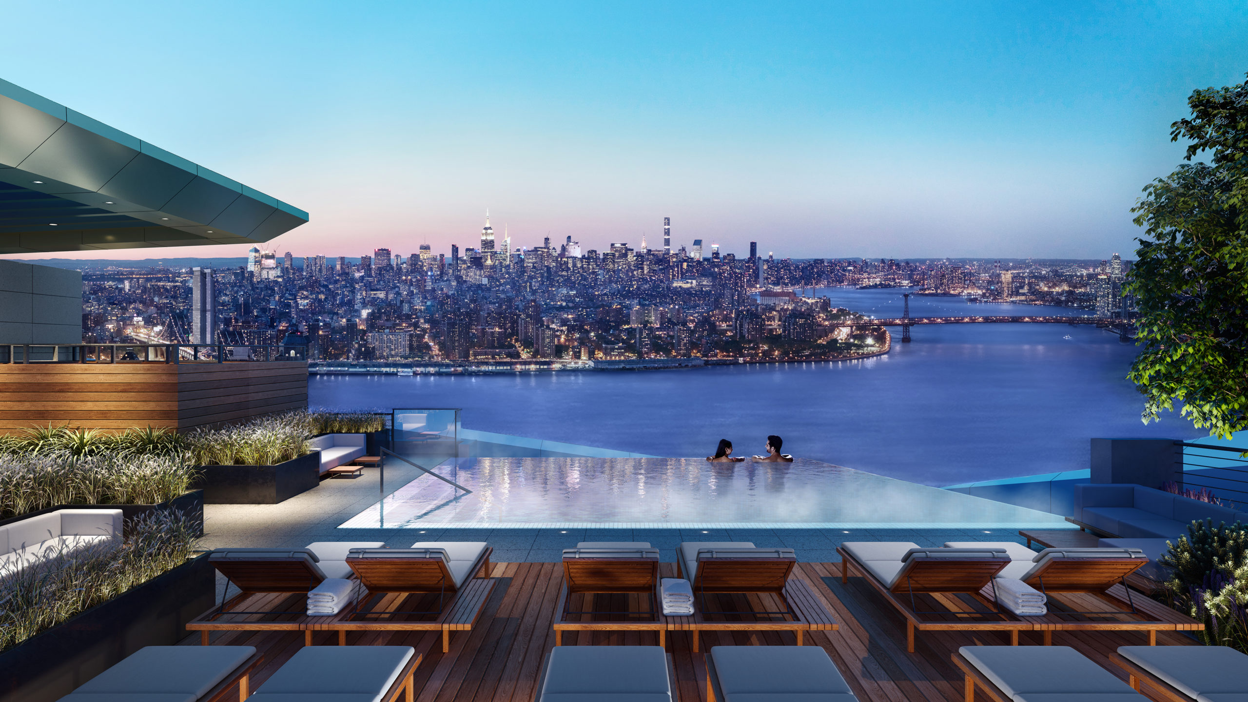 Exterior view of Brooklyn Point condominiums outdoor pool with view of river and Brooklyn buildings.