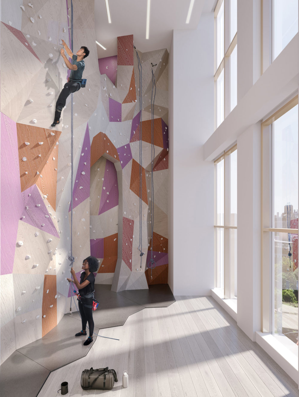 Interior view of Brooklyn Point residence rock climbing wall with window view. Has pink and orange rockwall.