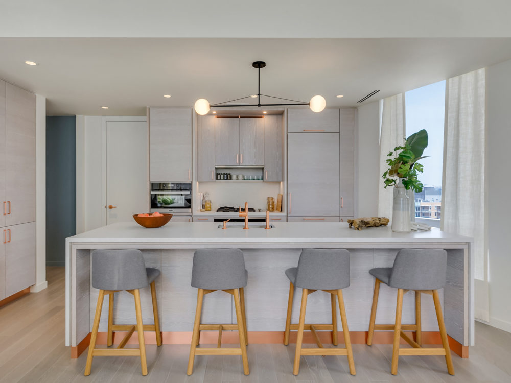 Interior view of Brooklyn Point residence kitchen with view of other buildings. Has white island countertop and wood floors.