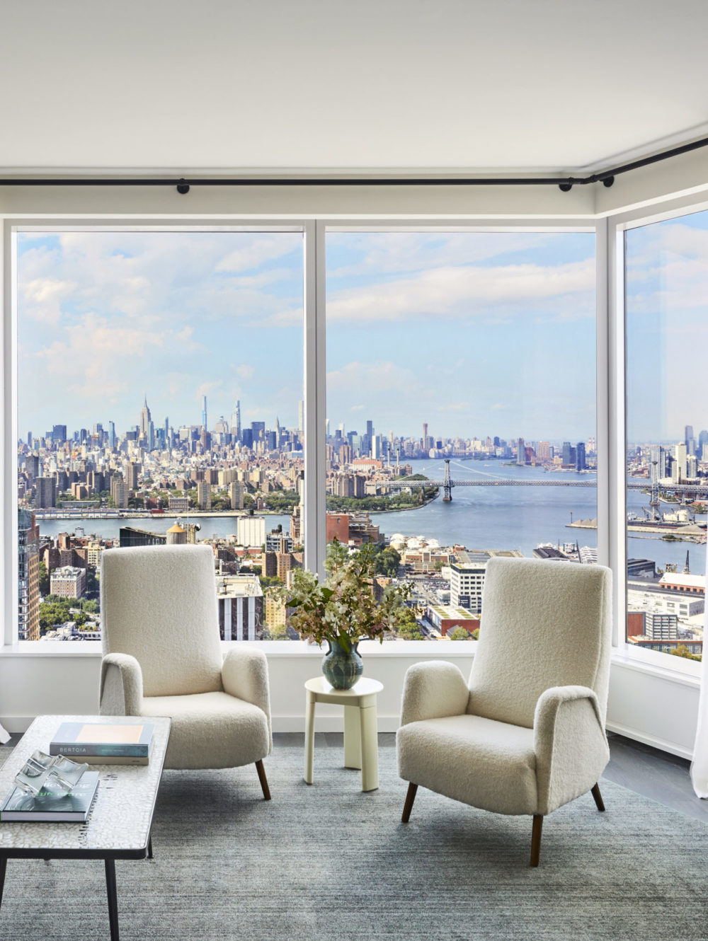 Interior view of Brooklyn Point residence living room with skyline window view. Has full furniture and white curtains.