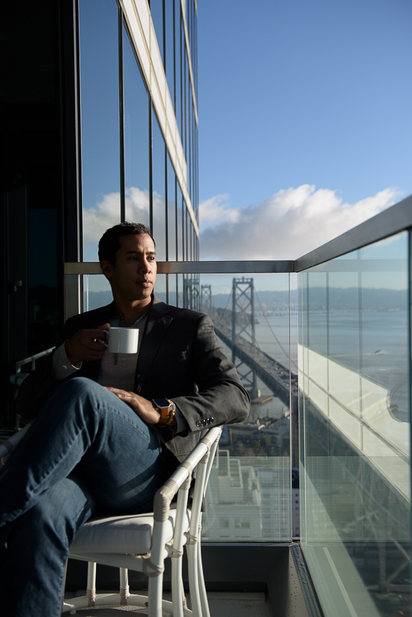 Private condo balcony at The Harrison in San Francisco. Glass railing and a man sitting in a chair looking at the Bay Bridge.