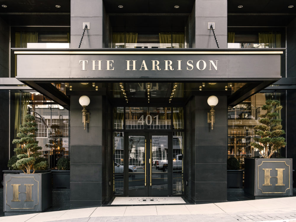 Front entrance to The Harrison luxury condominiums in San Francisco. Black framed doors and a canopy with the building name.