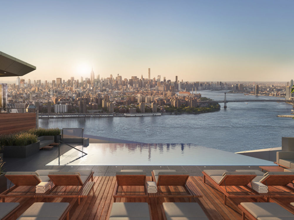 Exterior view of Brooklyn Point condominiums outdoor pool with river view and red lounging chairs in New York City.