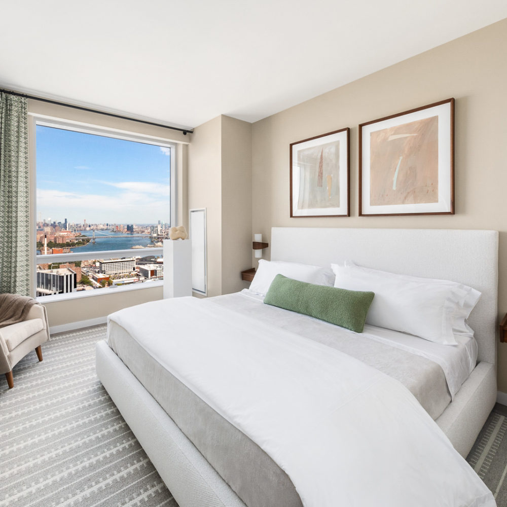 Interior view of Brooklyn Point residence master bedroom with skyline window view. Has striped carpets and white bed.