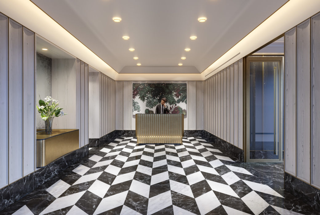 Interior view of lobby inside 40 East End Ave condominiums in NYC. Has checkered flooring, golden desk and white walls.