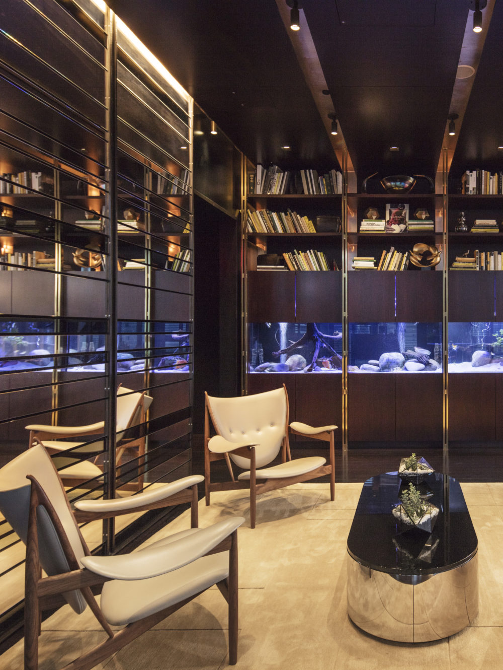 Residents library at One 57 condominiums in New York. Private library with dark wood shelves, aquarium, and four chairs.
