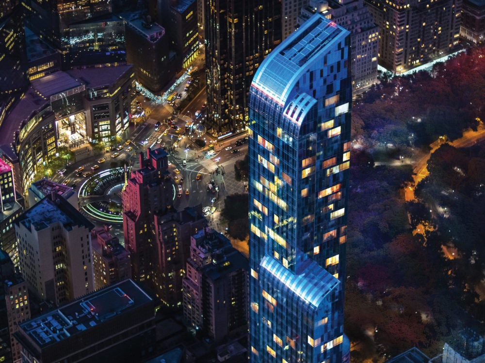 Night-time aerial view of One 57 luxury condominiums in New York City with lit up downtown background.