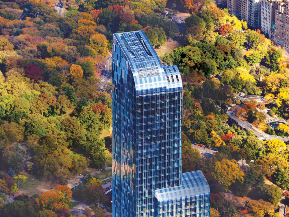 Exterior view of the top of One 57 luxury condos in NYC. Central Park in the background with city buildings lining the park.