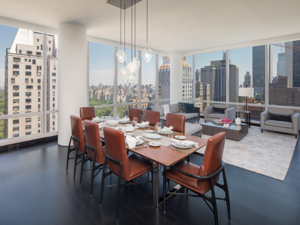 Dining room at One 57 condominiums in New York. Dining table, chairs and floor-to-ceiling windows with views of the city.