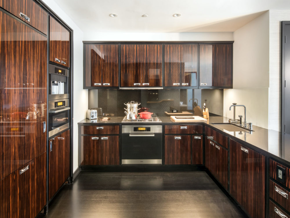 Kitchen in One 57 luxury condos in New York. Wood cabinets, white walls, stainless steel appliances and waterfall countertop.