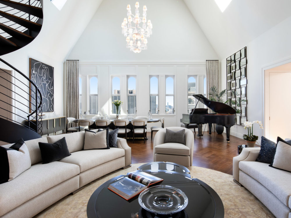 Open plan living room in the Woolworth Tower, NYC. Lofted ceilings, white walls, black spiral staircase, and chandelier.