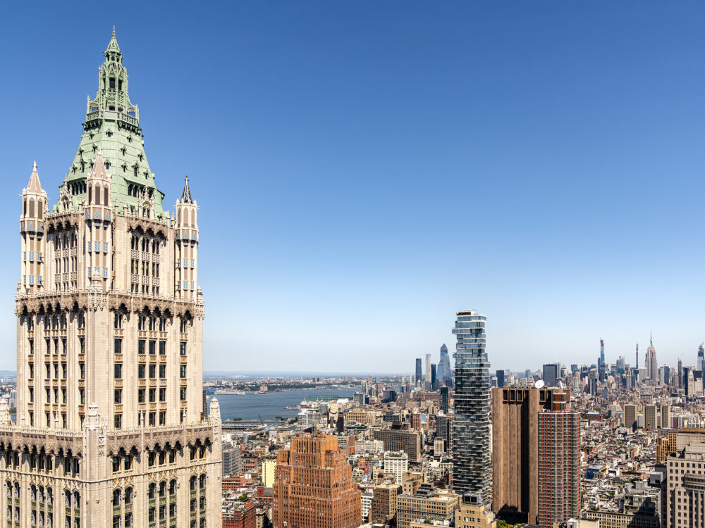 Birdseye view of the Woolworth Tower penthouse in New York. Downtown skyline of NYC in the background with blue skies.