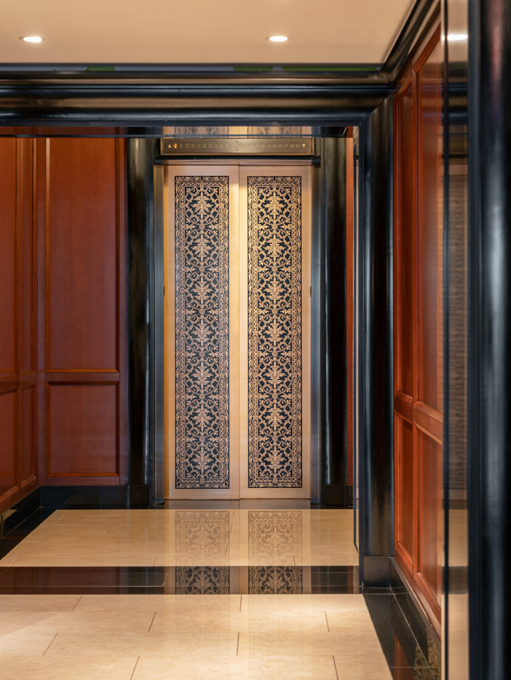 Elevator lobby at the Woolworth Tower condos in New York. Dark wood walls with black finishings and a gold elevator gate.