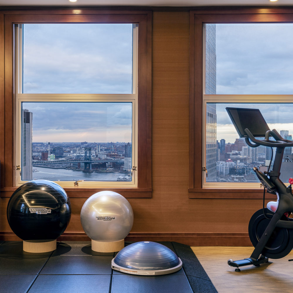 Fitness studio at the Woolworth Tower Residences in New York City. New cardio and conditioning equipment and city views.
