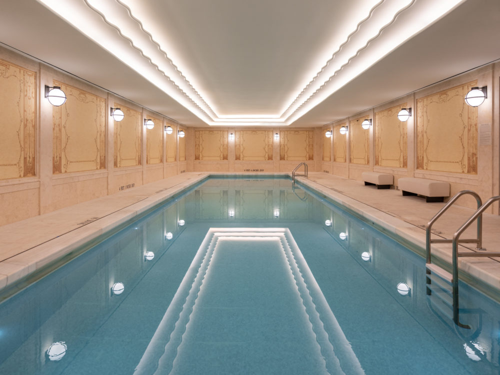 Underground 50-ft lap pool at the Woolworth Tower in New York. White ceiling with lights running the length of the pool.