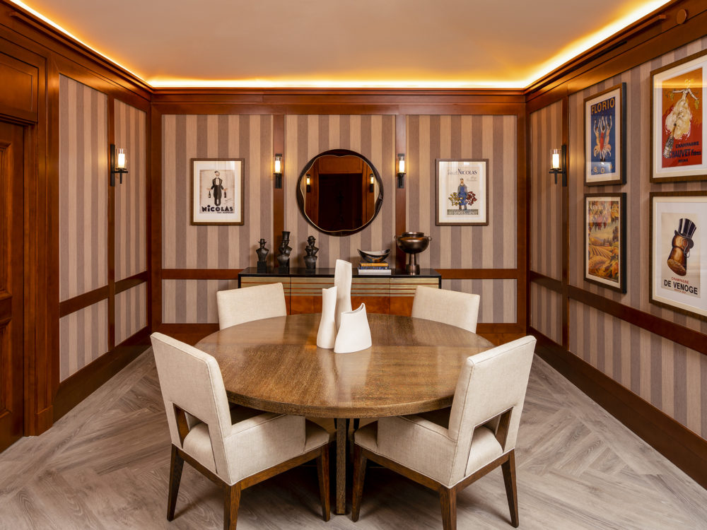 Dining room with small round table, 4 white chairs, and pinstriped wall paper in the Woolworth Tower condominiums, NYC.