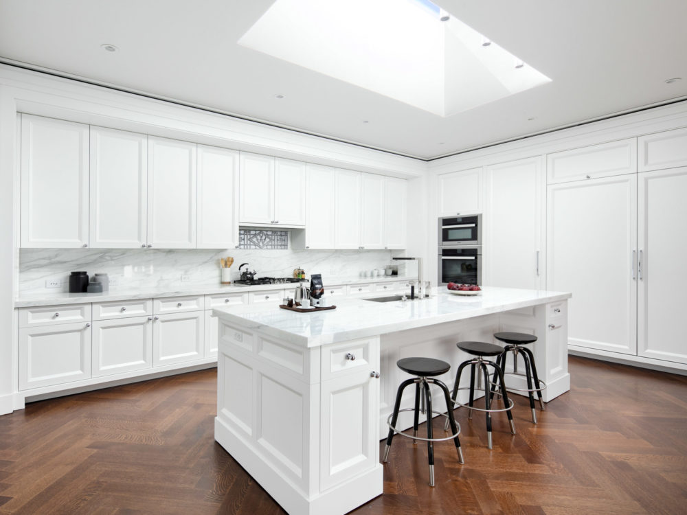 All white kitchen in the Woolworth Tower condos in NYC. White cabinets, marble countertops and dark hardwood floors.