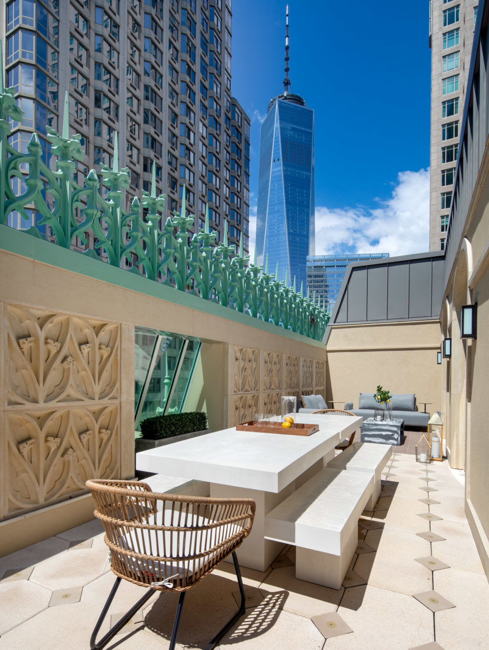 Balcony terrace at the Woolworth Tower Residences in New York. Sunlit patio with long white table, tan walls & skyline views.