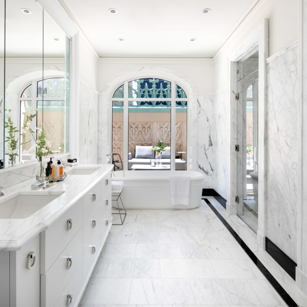 Condominium bathroom at the Woolworth Tower in New York. All white bathroom with marble floors, double vanity and bath tub.
