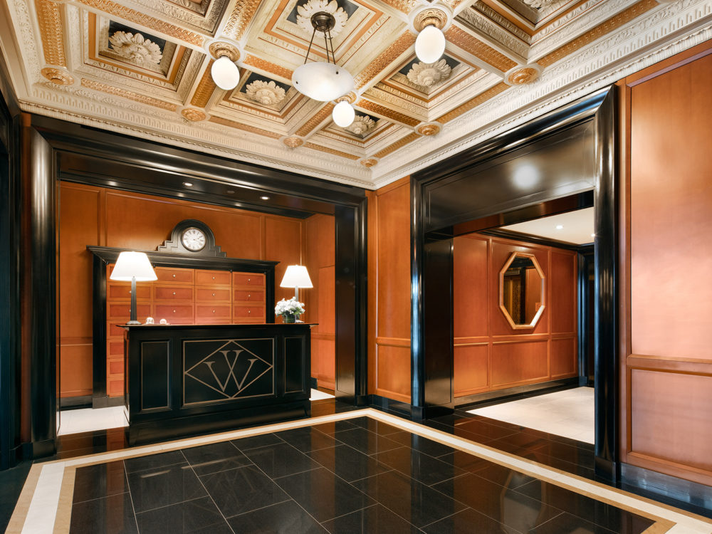 Lobby at Woolworth Tower in New York. Black, white & gold marble floors, Terra-cotta tile ceilings, and black front desk.