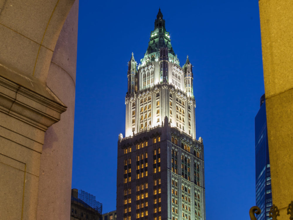 Exterior view of the Woolworth Tower in NYC. Street level view looking up at the high rise at night with tower lit up.