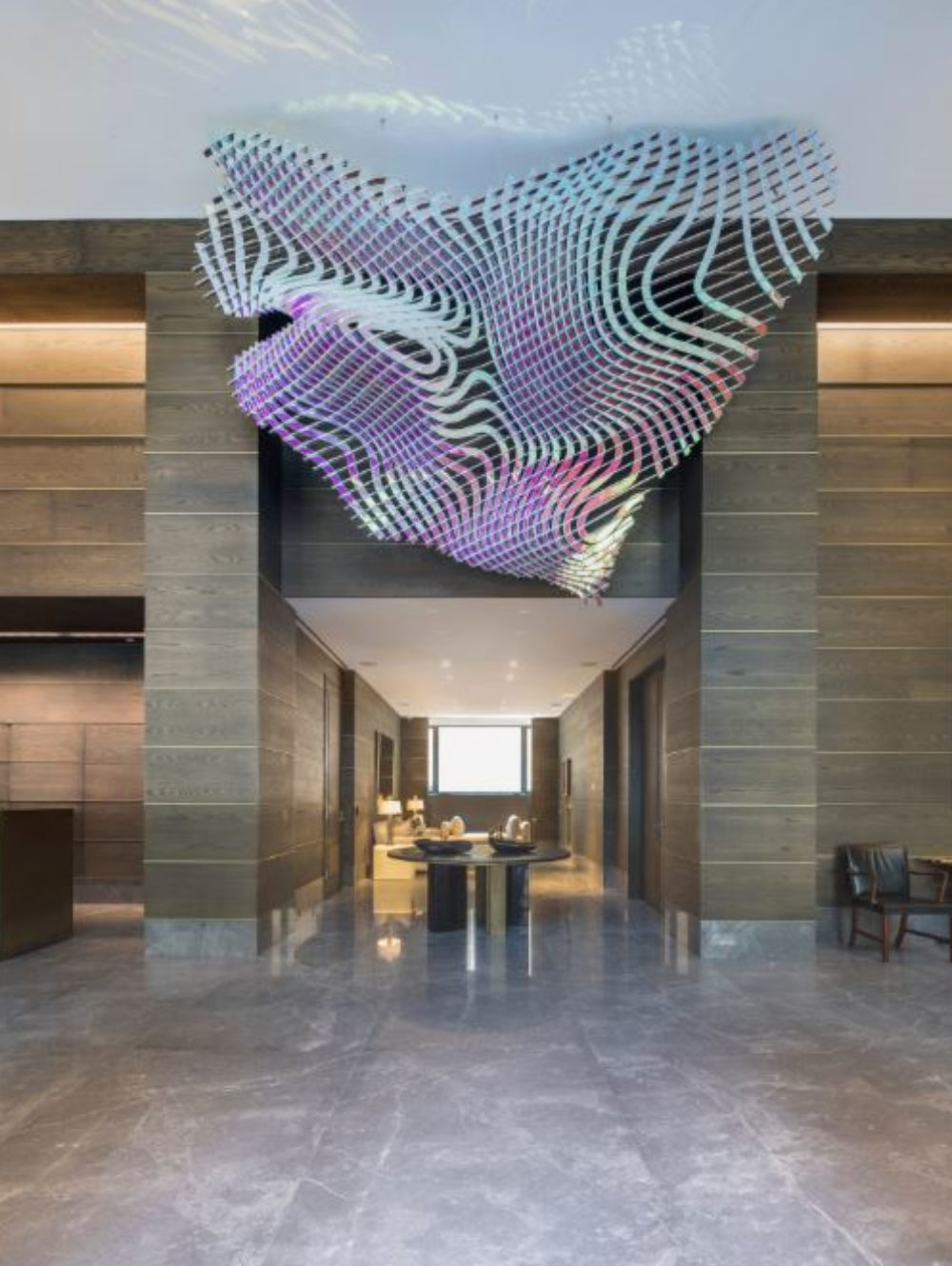 Interior view of 70 Vestry residence lobby in New York City. Has tile flooring, detailed fluorescent sculpture and tile walls.