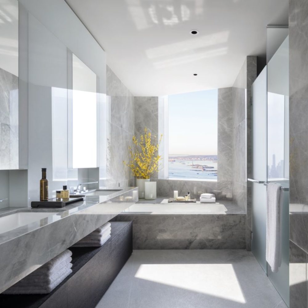 View of 15 Hudson Yards residence bathroom in New York City. Includes marble counters, tub and shower and big window.