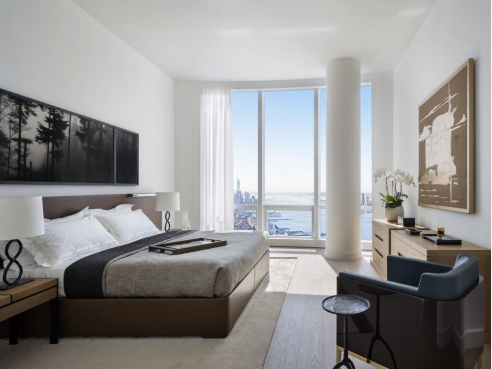 View of master bedroom in 15 Hudson Yards condominiums with a window view of New York City. Includes a large bed and pillows.