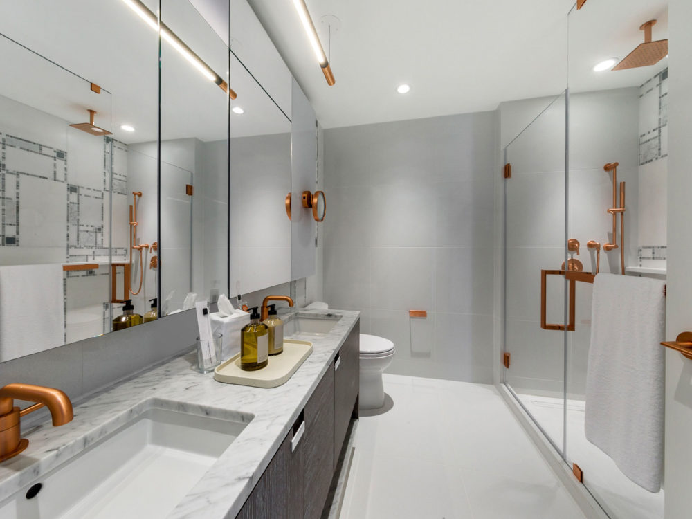 Interior view of Brooklyn Point residence master bathroom. Has marble counters and showers with gold trim.
