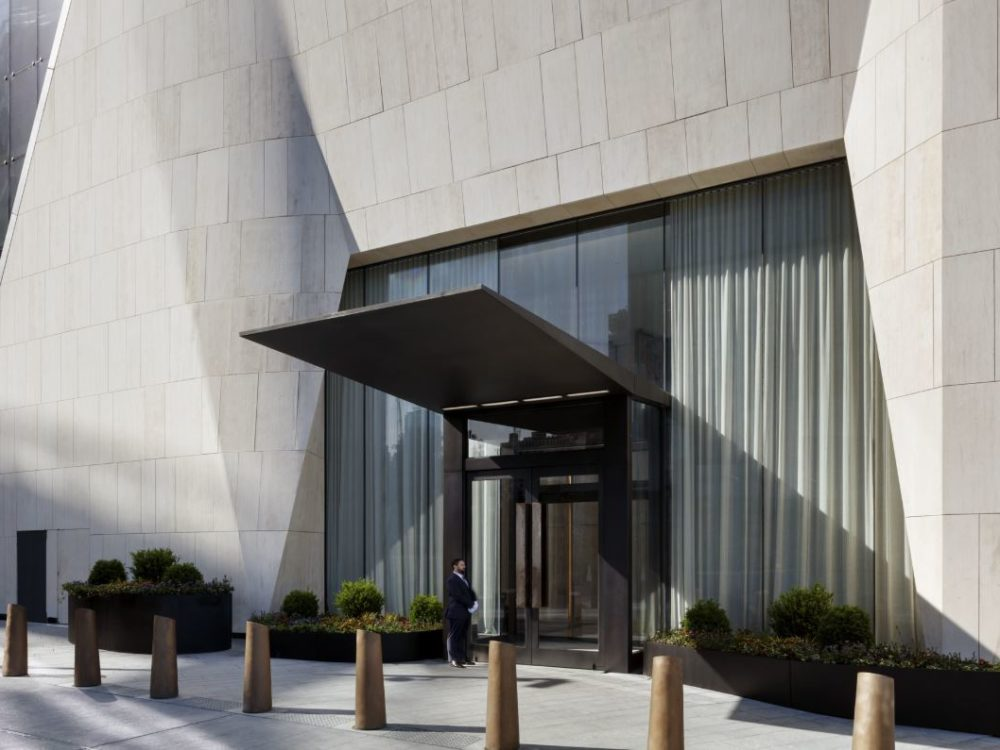 Exterior view on entrance to 15 Hudson Yards condominiums in New York City. White tile building with glass windows and doors.