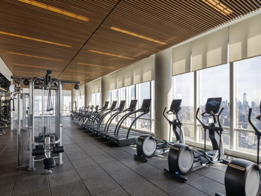 15 Hudson Yards condominiums fitness center with cardio and conditioning equipment with windows overlooking New York City.