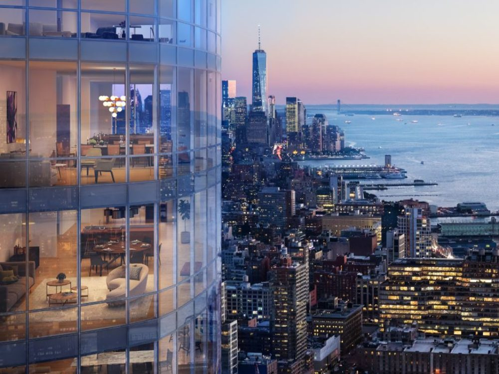 Exterior aerial view of 15 Hudson Yard condominiums with a view of New York City. Includes view of residential living room.